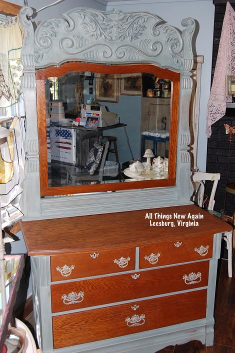 "The woodgrain was so pretty on this antique dresser and mirror that even I couldn't bear to paint over it! We restored the wood on the drawers and top then painted the frame and mirror with American Paint Company's ""Dollar Bill"", a soft, neutral grayish-green. $599"